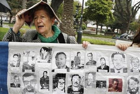 Member of Chilean human rights group Detained and Disappeared displays images of people who vanished during August Pinochet's dictatorship