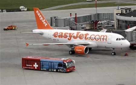 A bus carrying passengers passes an Easyjet aircraft at Cointrin airport in Geneva