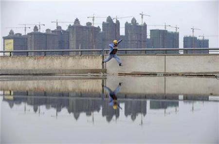 A worker jumps over a puddle near a residential construction site in Taiyuan, Shanxi province
