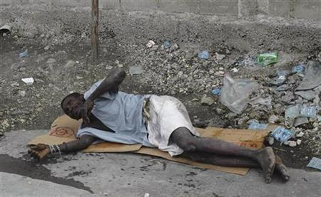 A Haitian resident suffering from cholera waits for help on a street at the slum of Cite-Soleil in Port-au-Prince