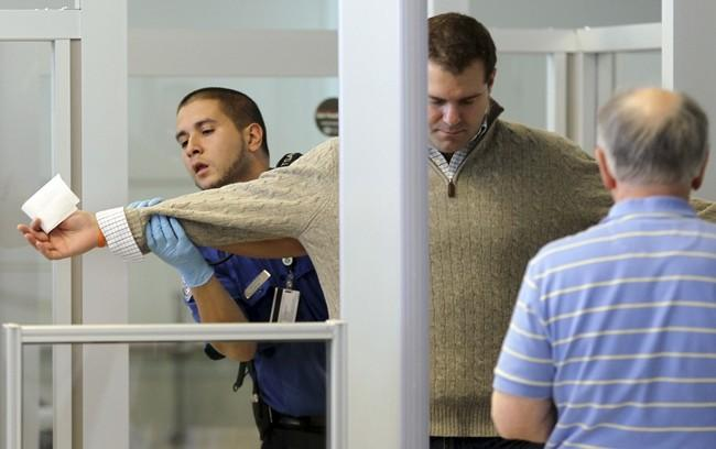 A U.S. Transportation Security Administration (TSA) officer carries out a physical search on a passenger at a security checkpoint at Newark Liberty International Airport in New Jersey December 29, 2009.