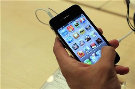 A customer looks at an iPhone 4 at the Apple Store 5th Avenue in New York