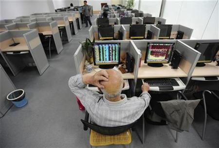 An investor scratches his head in front of a computer screen showing stock information at a brokerage house in Hefei