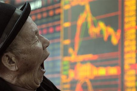 A man yawns in front of an electronic board showing stock information at a brokerage house in Taiyuan