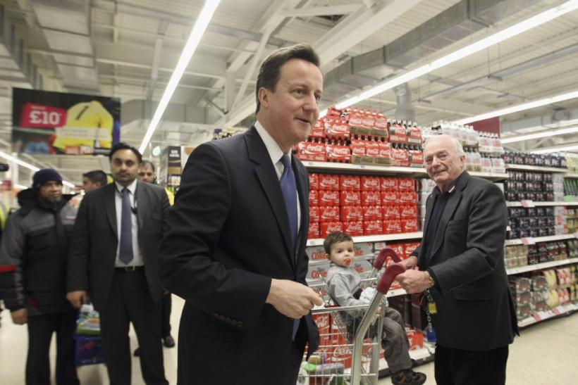 Britain's Prime Minister David Cameron (C) walks around a branch of Sainsbury's supermarket during a visit, in east London February 17, 2011.