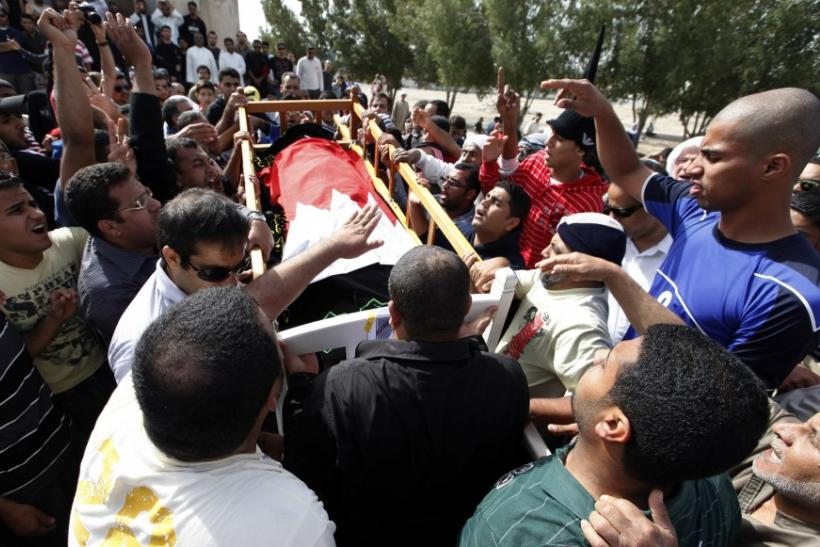 The body of a protester is taken for burial as his family members and supporters follow in Sitra