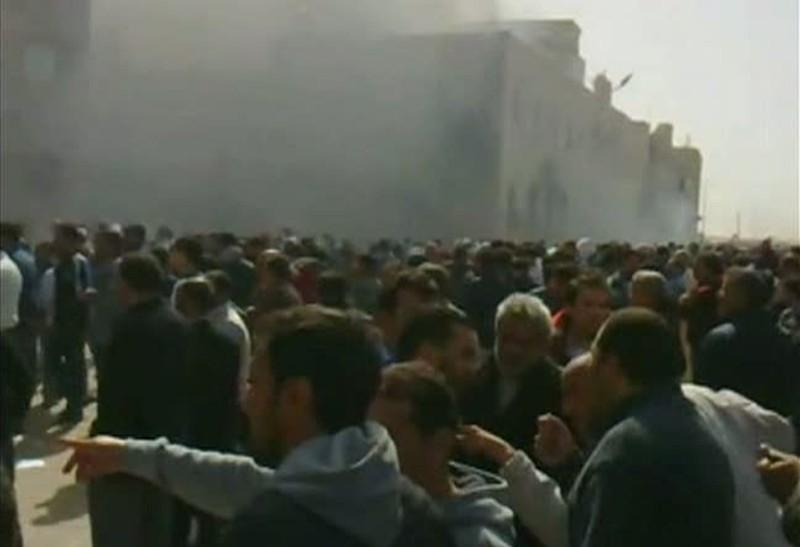 Frame grab shows a crowd gathering as smoke billows from a building in Benghazi