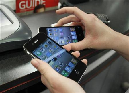 Customer holds iPhones she purchased shortly after the phone went on sale with the Verizon Wireless network in Boca Raton, Florida