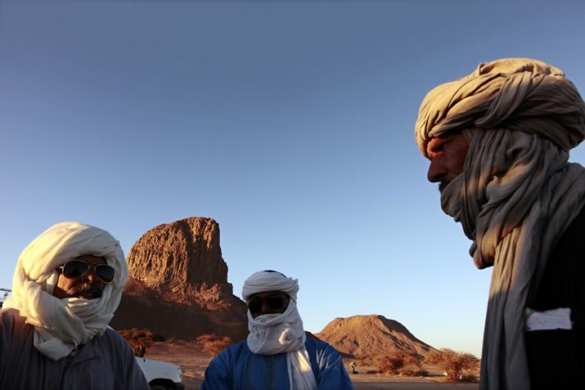 Tuareg men stand in front of the Iharen peak near southern city of Tamanrasset