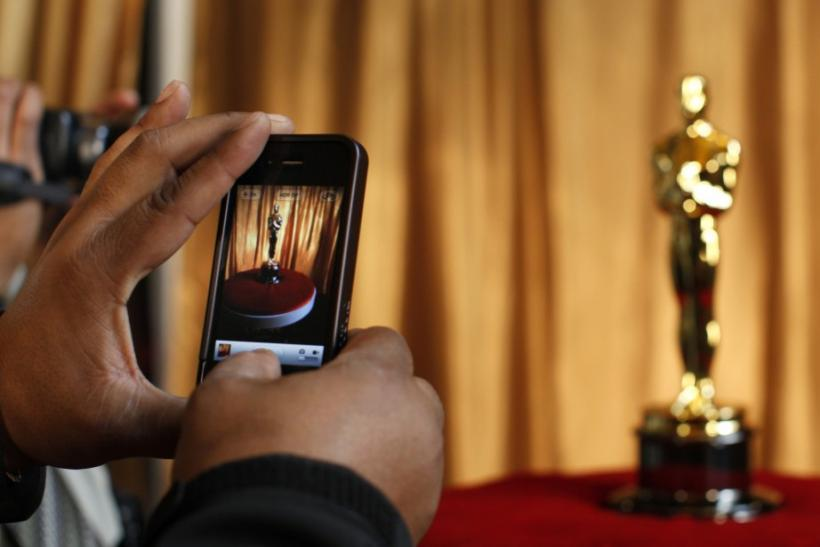 """A man photographs an Oscar statuette using his phone at the """"Meet the Oscars"""" exhibit at Grand Central Station in New York February 23, 2011"""