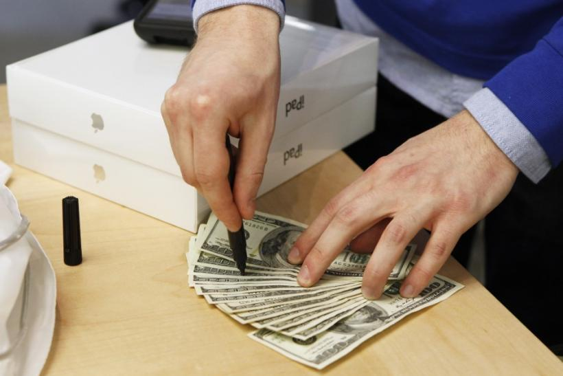 An Apple store employee checks cash for counterfeit bills after a customer purchased a pair of Apple iPad 2 tablets in New York