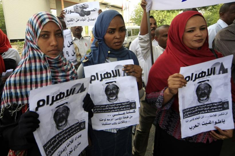 Protesters hold pictures of Al Jazeera cameramen Ali Hassan al-Jaber during a rally against the assassination of journalists in Khartoum