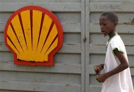 A file photo shows a Nigerian boy walking past the logo of Dutch oil giant Shell near Warri in the volatile Niger-Delta