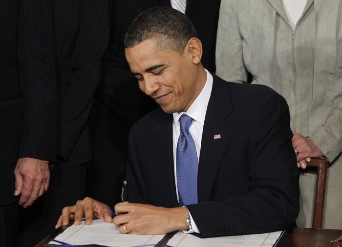U.S. President Obama signs healthcare legislation in the East Room of the White House in Washington