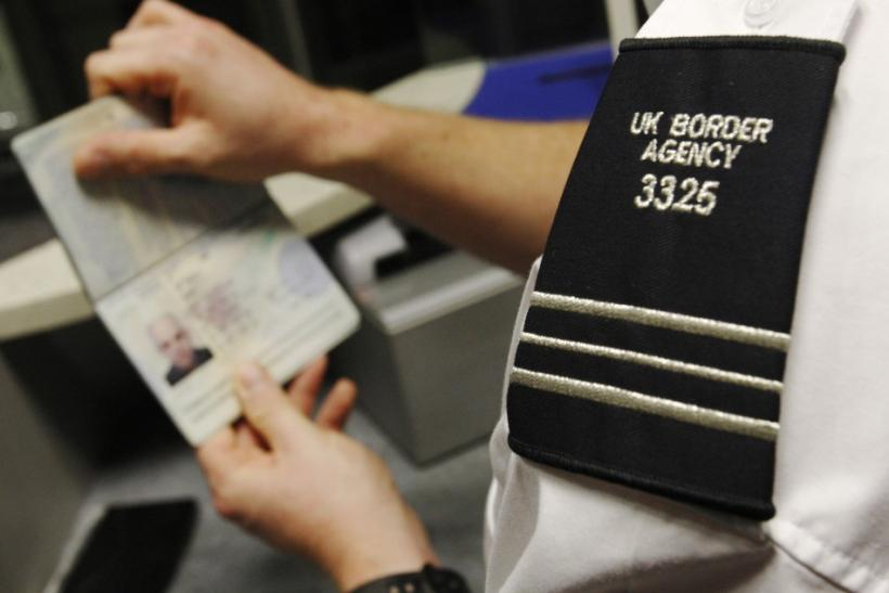 A UK Border Agency worker poses with a passport during a demonstration