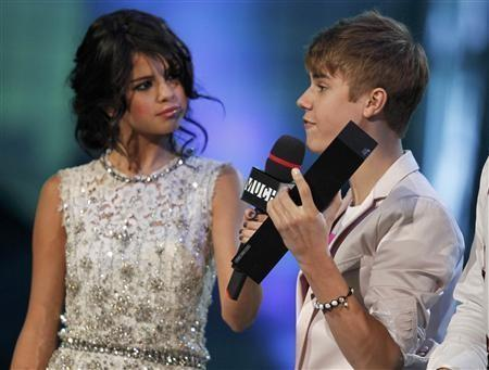 "Justin Bieber accepts the award for ""Ur Fav Artist"" for his song ""Somebody to Love"" from host Selena Gomez during the MuchMusic Video Awards in Toronto, June 19, 2011."