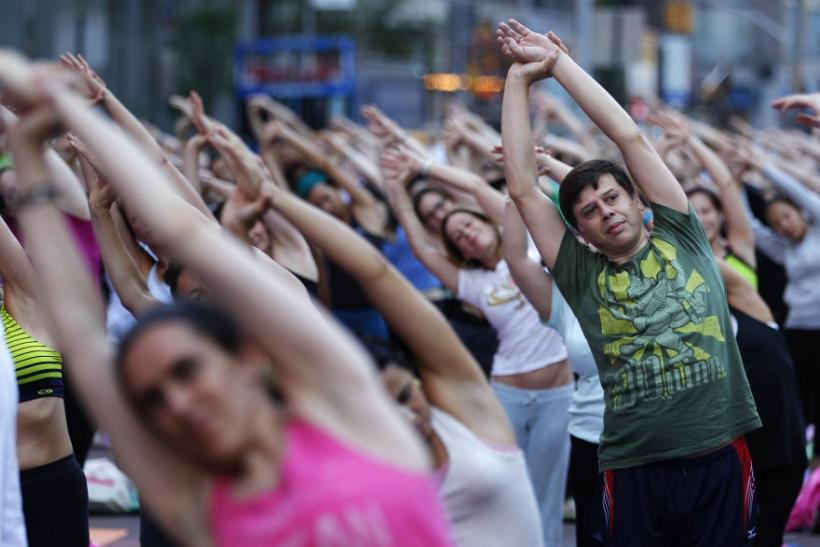 """People practice yoga on the morning of the summer solstice in New York's Times Square June 21, 2010. The eighth annual """"Solstice in Times Square"""" event on Monday brought out thousands of participants to celebrate the year's longest day"""