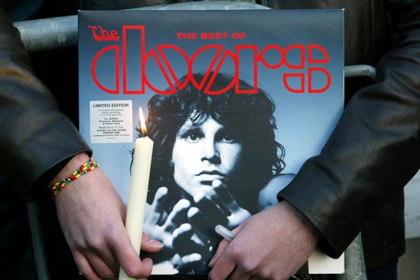 A fan holds an album by the seventies rock group The Doors and a candle near the tomb of late singer..