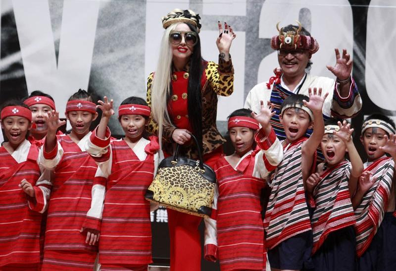 U.S. singer Lady Gaga waves to the audience with children