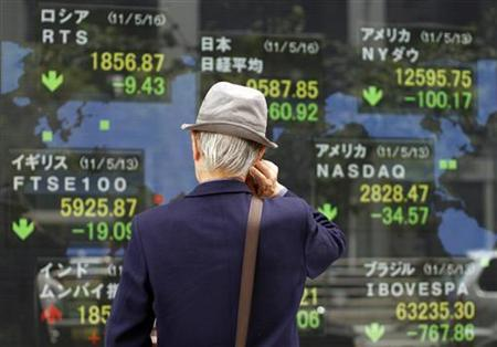 Man looks at an electronic board displaying various market indices from around the world outside a brokerage in Tokyo