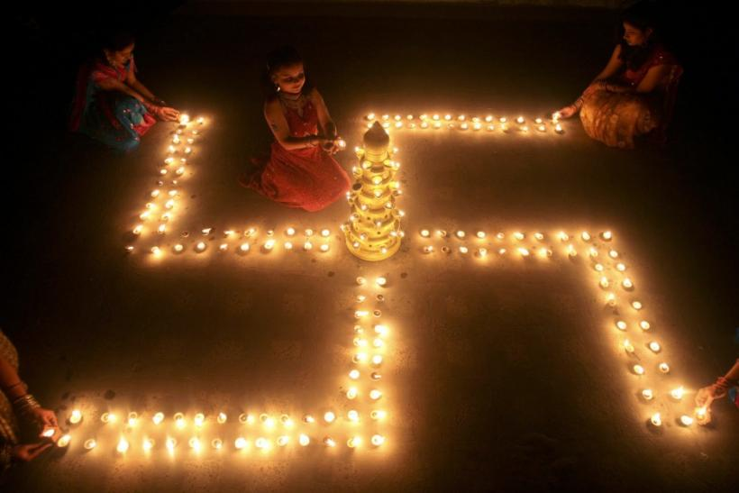 People light earthen lamps in a formation of the 'Swastika', a Hindu symbol of peace, a day before the Hindu festival of Diwali, the festival of lights, in the western Indian city of Ahmedabad
