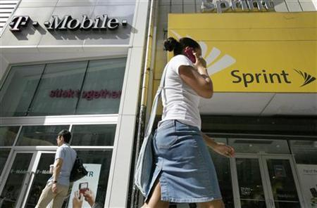 A woman talks on her phone as she walks past T-mobile and Sprint wireless stores in New York