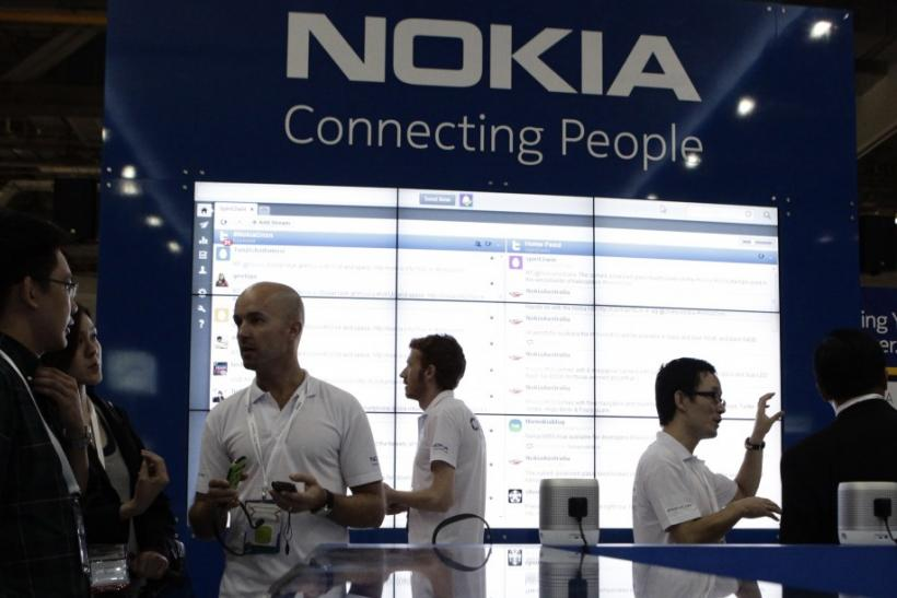 Staff members speak to trade visitors at the Nokia booth at the CommunicAsia expo in Singapore