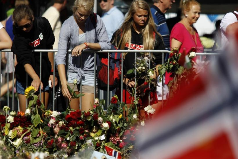 A woman cries as she pays her respects for the victims of attacks outside the Oslo cathedral