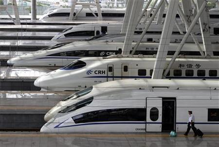 A train employee prepares to enter a CRH (China Railway High-speed) Harmony bullet train at Beijing South Railway Station