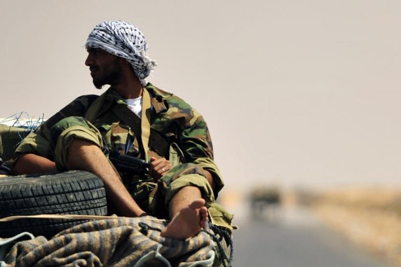 A Libyan rebel is seen near the entrance of Ras Lanuf oil refinery