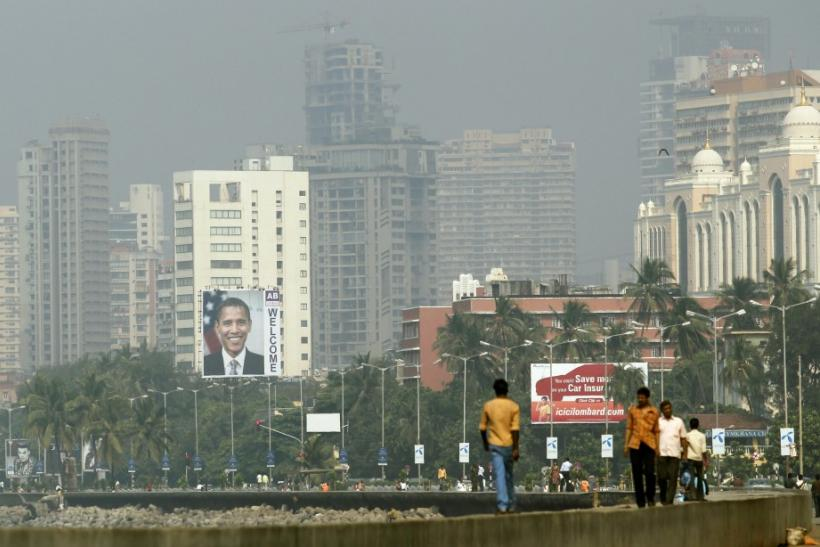 Residents walk in the city as a big banner of of U.S. President Barack Obama is pictured on a building, in Mumbai