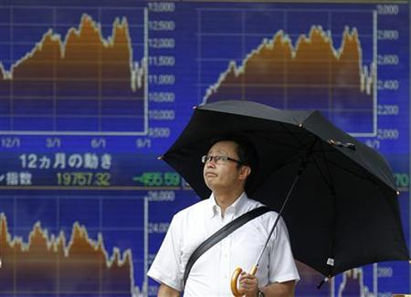 A man waits to cross a street in front of an electronic board displaying major stock market indices outside a brokerage in Tokyo