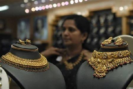 An Indian woman tries on a gold necklace inside a jewellery shop in Hyderabad May 14, 2010.