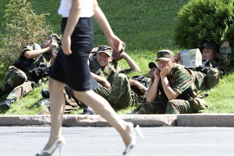 Army servicemen sit on the ground as they watch a woman walk past, while waiting for instructions, during a rally near the parliament headquarters in Bishkek