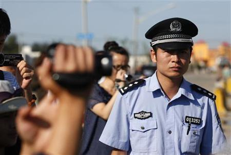 A policeman looks at journalists filming during the verdict hearing of Chinese rights activist Wang Lihong outside a courthouse in Beijing