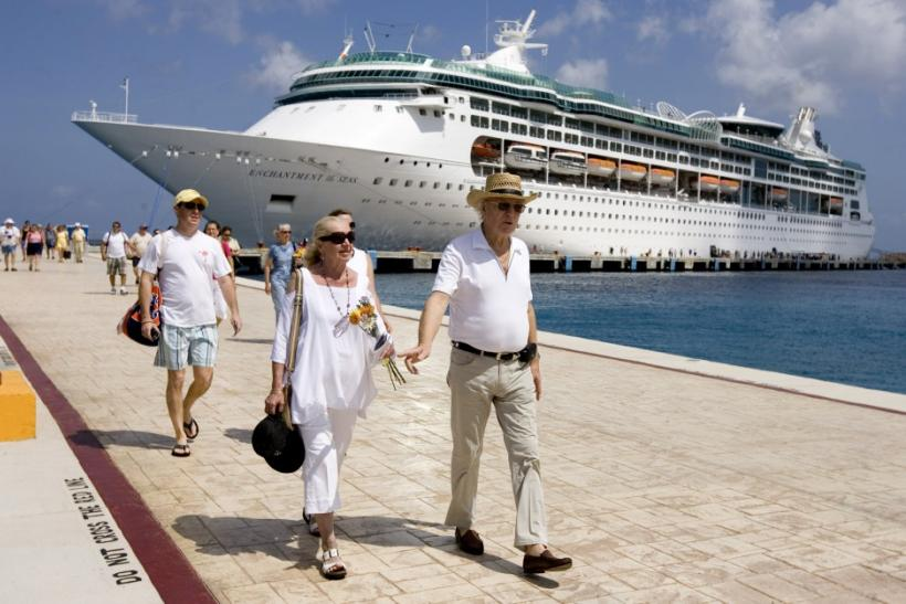 Tourists walk beside Royal Caribbean's cruise ship ?Enchantment of the Seas