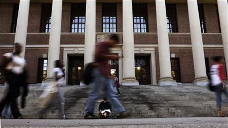 A students sits on the steps of Widener Library at Harvard University in Cambridge