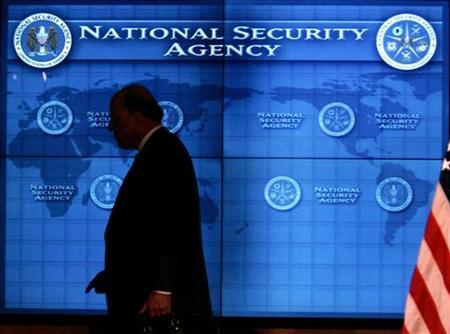 National Intelligence Director John Negroponte past a video screen at National Security Agency at Fort Meade