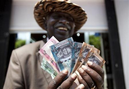 A man from South Sudan displays new currency notes outside the Central Bank of South Sudan in Juba