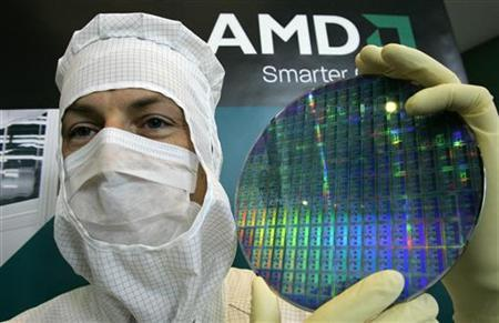 A technician of computer microprocessors maker AMD poses for the media with a wafer at the chip plant in Dresden