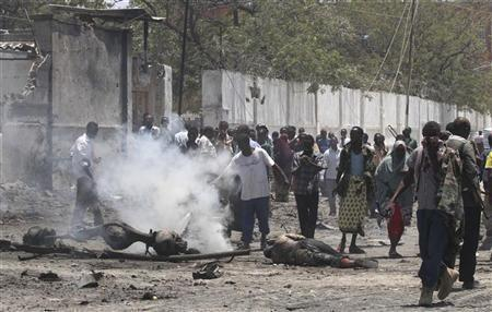 """Residents gather at the scene of a suicide attack in Somalia""""s"""