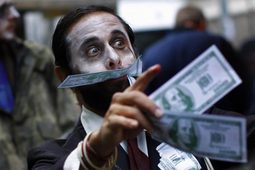 """A demonstrator carries play money while dressed as a """"corporate zombie"""" as he walks with others taking part in an Occupy Wall Street protest in lower Manhattan in New York"""