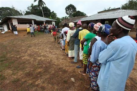 People wait to vote during the presidential election at a polling station in Liberia