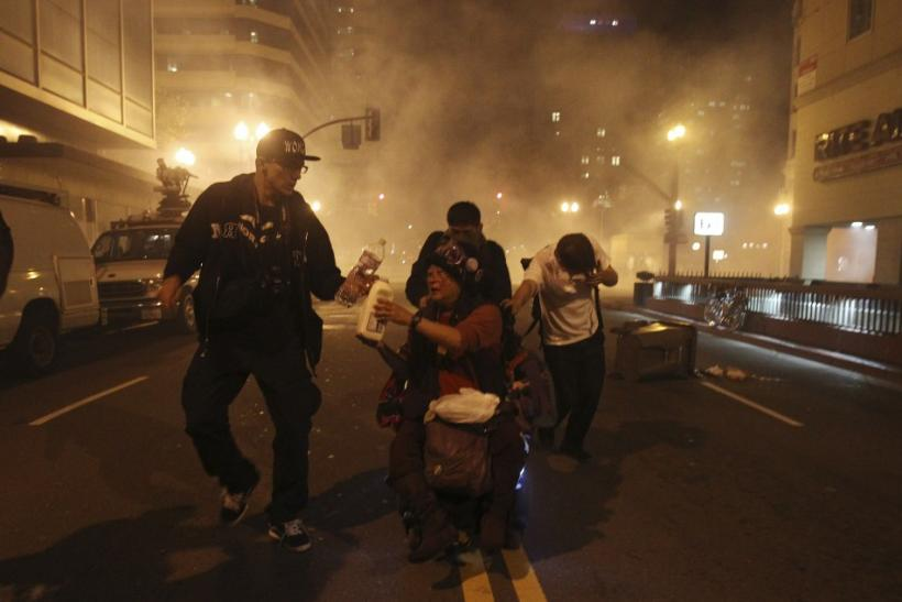 An Occupy Wall St. demonstrator in a wheelchair is pushed away as authorities deploy tear gas during an demonstration in response to an early morning police raid which displaced Occupy Oakland's tent city in Oakland, California