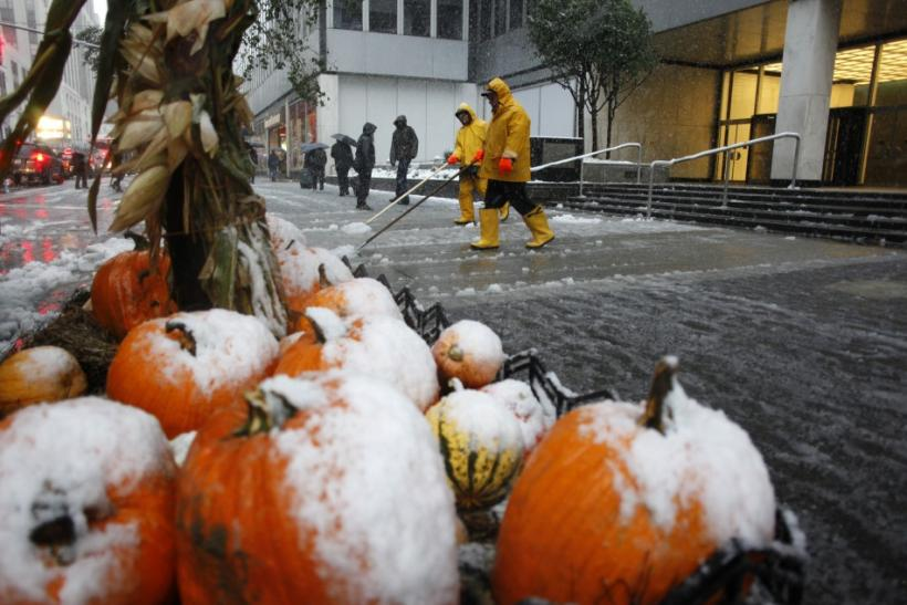 Workers clear snow from the sidewalks as a decorative display of pumpkins are coated in snow in New York, October 29, 2011. A rare October snowstorm bore down on the heavily populated U.S. Northeast on Saturday, with some areas bracing for up to a foot (3