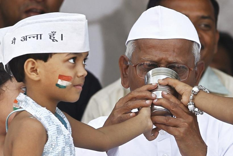 A child offers coconut water and honey to Indian social activist Hazare to end his fast in New Delhi