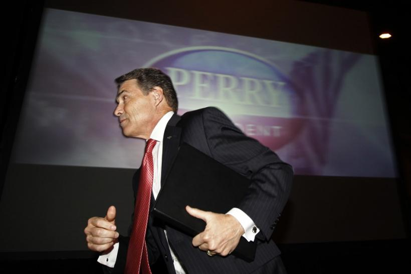 U.S. Republican presidential candidate and Governor of Texas Rick Perry runs up on to the stage to speak at the annual Republican Party of Iowa Ronald Reagan Dinner in Des Moines, Iowa, November 4, 2011.