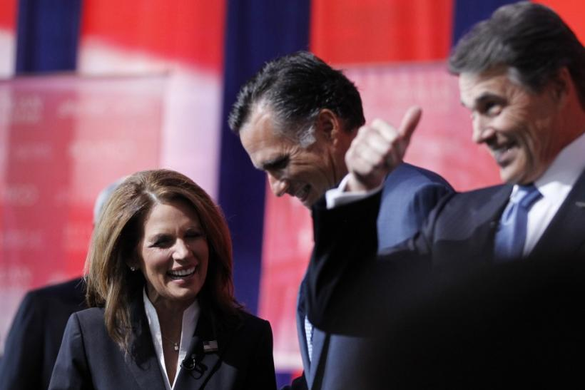Rep. Michele Bachmann (R-MN) talks to former Massachusetts Governor Mitt Romney (C) and Texas Governor Rick Perry (R) on stage before the Reagan Centennial GOP presidential primary debate at the Ronald Reagan Presidential Library in Simi Valley, Californi