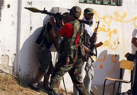 A Libyan rebel fighter prepares to fire a rocket propelled grenade launcher