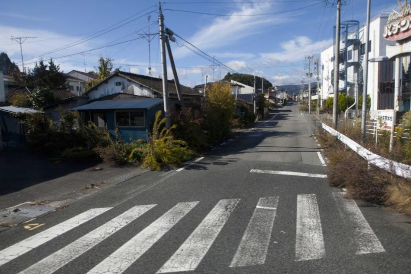 A deserted street inside the contaminated exclusion zone around the crippled Fukushima Daiichi nuclear power plant is seen from bus windows